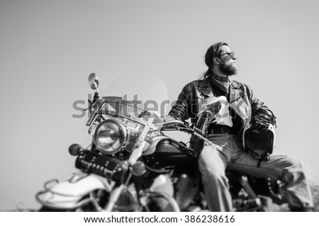 Portrait of a young man with beard sitting on his cruiser motorcycle. Man is wearing leather jacket and blue jeans. Low point of view. Tilt shift lens blur effect. Black and white - stock photo