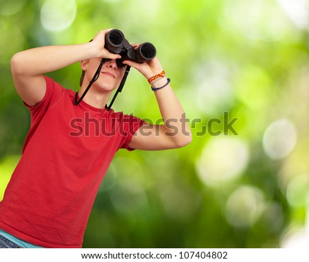 portrait of a young man with binoculars against a nature background - stock photo