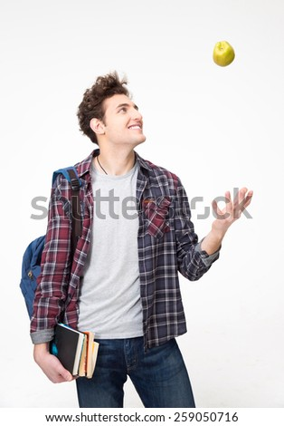Portrait of a young man with book and an apple - stock photo