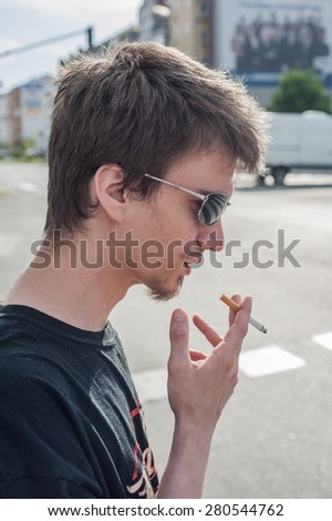 portrait of a young man with cigarette - stock photo