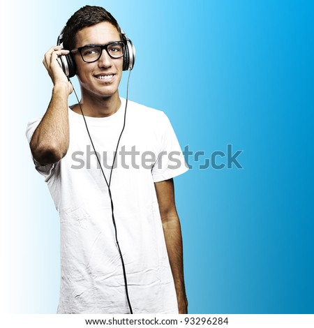 portrait of a young man with glasses and headphones listening to music on a blue background - stock photo