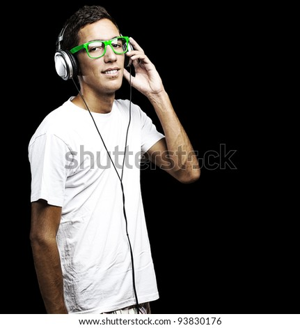 portrait of a young man with green glasses listening to music with headphones against a black background - stock photo
