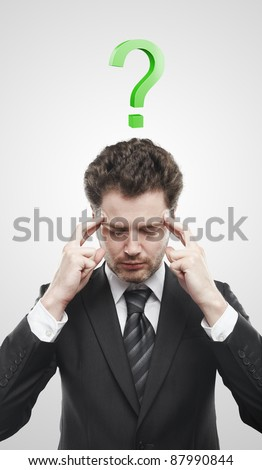Portrait of a young man with green question mark above his head.Conceptual image of a open minded man. On a gray background - stock photo