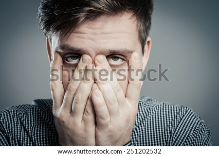Portrait of a young man with his hand on his eyes - stock photo