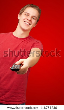 portrait of a young man with remote control on red background - stock photo