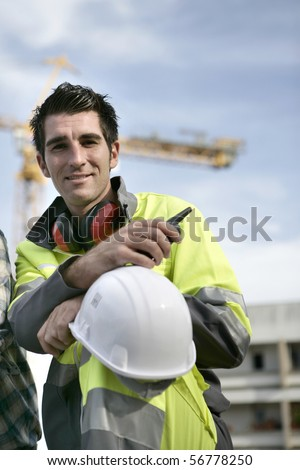 Portrait of a young man with safety vest and noise-canceling headphones - stock photo
