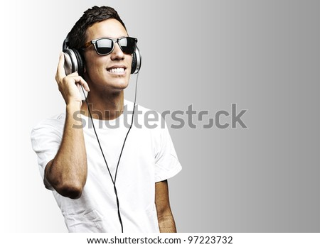 portrait of a young man with sunglasses playing to music on a grey background - stock photo