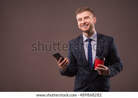 Portrait of a young man with the phone and coffee cup in hand