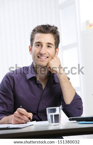 Portrait of a young man working at desk