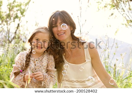 Portrait of a young mother and daughter relaxing together during a sunny holiday, holding their heads together, looking at floating bubbles in a green field. Family activities lifestyle, outdoors. - stock photo