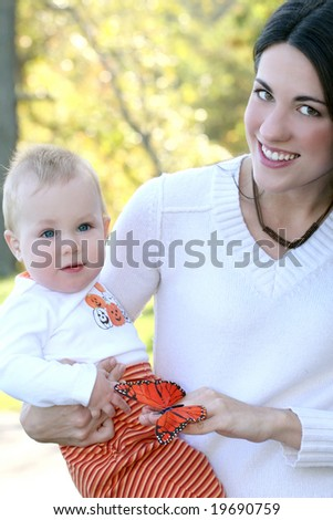 Portrait of a young mother and her blue-eyed baby boy with bright orange and red butterfly, outdoors in a park, suitable for a variety of seasonal and family themes - stock photo