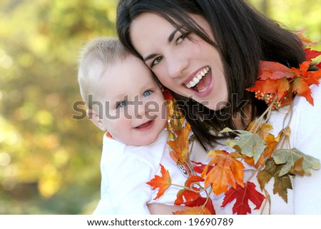 Portrait of a young mother and her blue-eyed baby boy with bright orange and yellow leaves, outdoors in a park, suitable for a variety of seasonal and family themes - stock photo