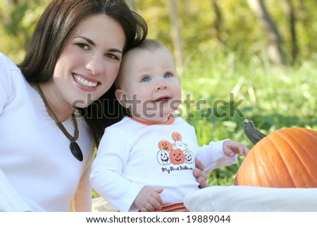Portrait of a young mother and her blue-eyed baby boy with bright orange pumpkin, outdoors in a park, suitable for a variety of seasonal and family themes - stock photo