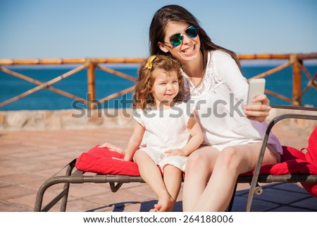 Portrait of a young mother and her daughter taking a selfie with a smartphone and smiling - stock photo
