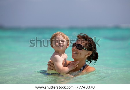 Portrait of a young mother with a cute toddler in her hands in turquoise water