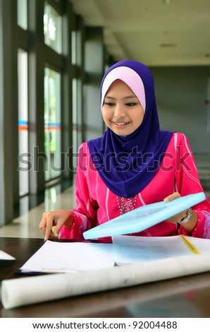 Portrait of a young Muslim architect-woman busy