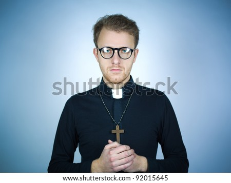Portrait of a young pastor wearing a black shirt and clerical collar with a rosary and cross around his neck as he clasps his hands in prayer. - stock photo