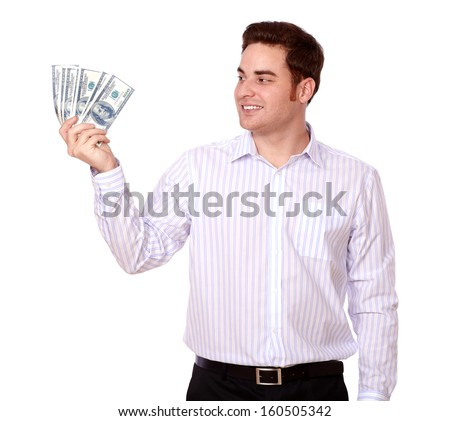 Portrait of a young person holding and looking at cash dollars while smiling and standing on isolated studio
