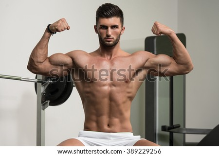 Portrait Of A Young Physically Fit Man Resting On Bench And Showing His Well Trained Body - stock photo