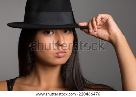 Portrait of a young pretty asian girl in a black hat. - stock photo