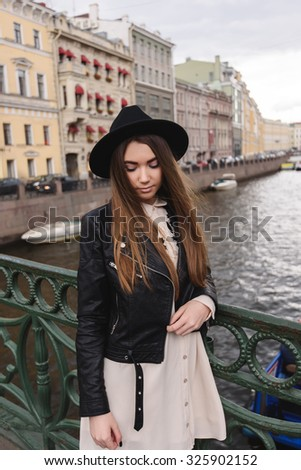 Portrait of a young pretty fashionable woman posing while standing on a river bridge on a cloudy spring day, attractive female tourist with trendy look walking on the city during her recreation time - stock photo