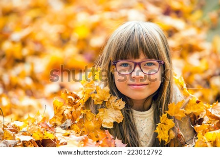 Portrait of a young pretty girl who was cheerfully playing with autumn maple leaves.Autumn background from yellow-orange maple leaves - stock photo