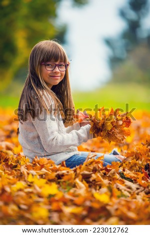 Portrait of a young pretty girl who was cheerfully playing with autumn maple leaves.Girl sitting on colorful autumn leaves. - stock photo