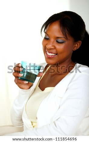 Portrait of a young pretty lady smiling and drinking fresh water while looking to the glass - stock photo