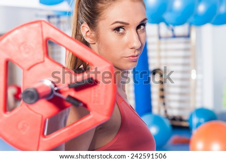 Portrait of a young pretty woman holding weights (dumbbell) and doing fitness indor. Crossfit hall. Gym shot. - stock photo