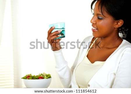 Portrait of a young pretty woman looking to a fresh water glass while smiling on a light background - stock photo