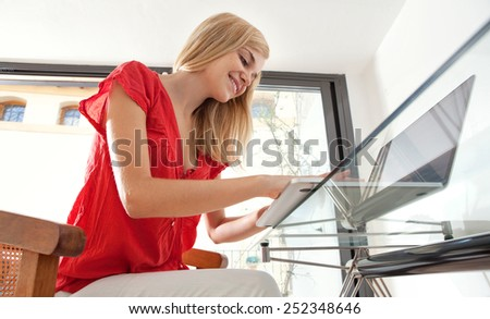Portrait of a young professional woman smiling in her home office space, typing and working on line. Student girl using a laptop computer at her home work desk. Lifestyle and technology, interior. - stock photo
