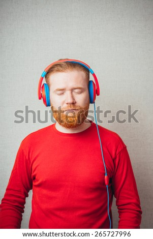 Portrait of a Young  red bearded Man singing and listening to music in headphones  - stock photo