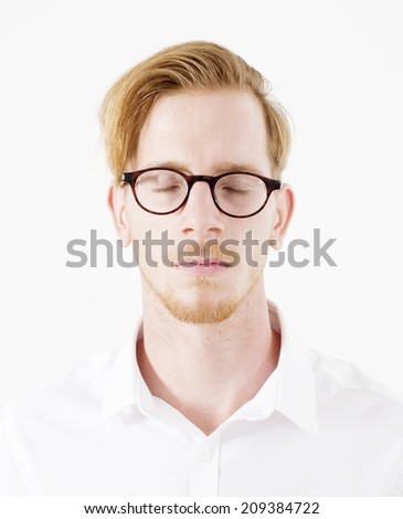 portrait of a young red-haired man with glasses in a white shirt with his eyes closed