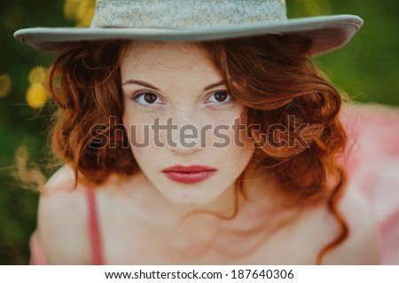 Portrait of a young redhead woman dressed - stock photo