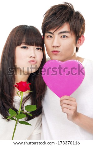 Portrait of a young romantic couple holding rose with heart box - stock photo
