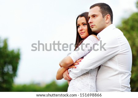 Portrait of a young romantic couple looking at copyspace outdoors - stock photo
