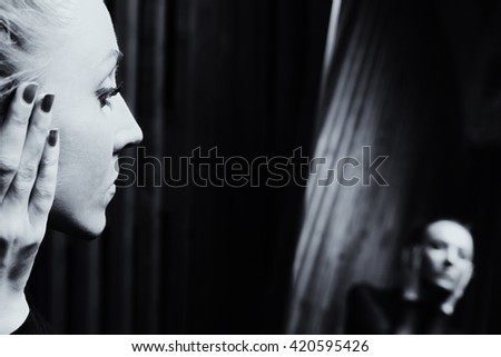Portrait of a young sad woman looking in the mirror - stock photo