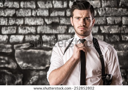 Portrait of a young, serious man is posing near a wall with a gun. - stock photo