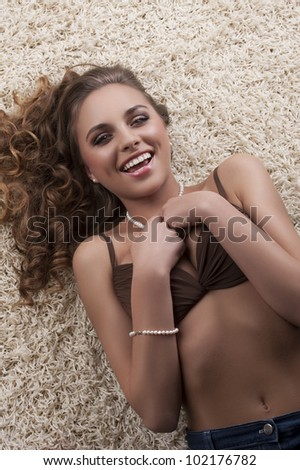 portrait of a young sexy girl in brown bra with a pearl necklace laying on a white modern carpet - stock photo