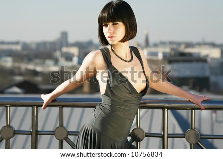 Portrait of a young sexy girl on the roof of the building - stock photo