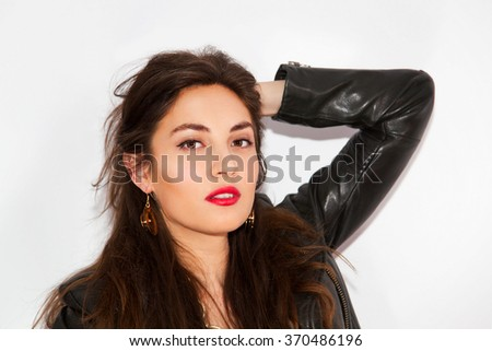 Portrait of a young sexy model woman with bright makeup wearing a black leather biker jacket and big golden accessories.  - stock photo