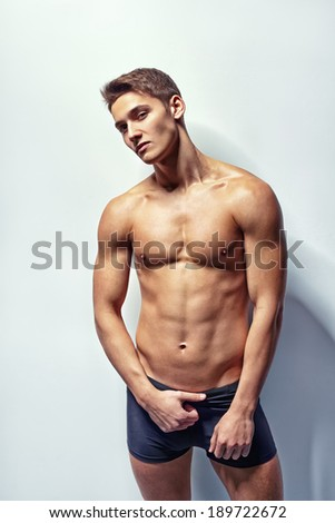 Portrait of a young sexy muscular man in underwear against white wall in sensual pose