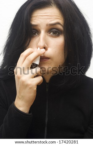 portrait of a young sick woman taking nose drops