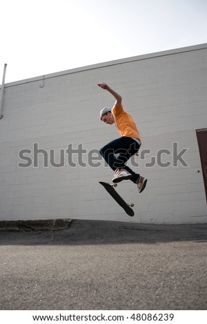 Portrait of a young skateboarder performing a trick in an urban setting. - stock photo