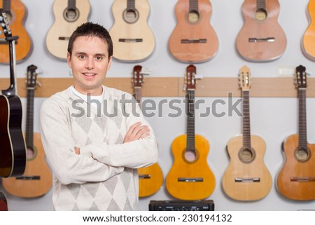 Portrait of a young small business owner, standing with display of guitars in background - stock photo