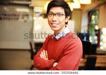 Portrait of a young smiling asian man with arms folded standing in office - stock photo