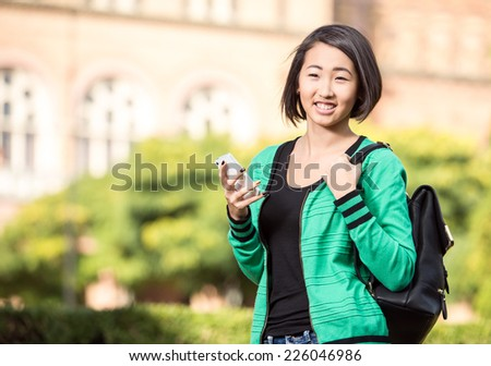 Portrait of a young smiling asian student with university building in the background. - stock photo