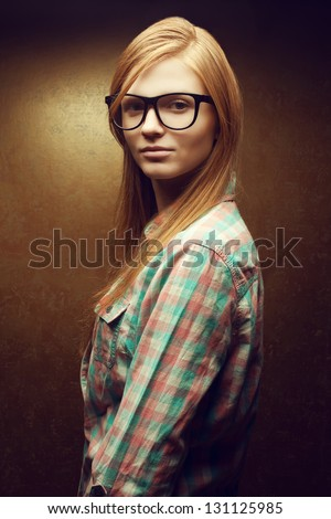 Portrait of a young smiling beautiful red-haired (ginger)  woman wearing trendy glasses and casual shirt. Girl  posing over golden background. Studio shot.