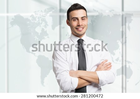 Portrait of a young smiling businessman in front of a world map - stock photo