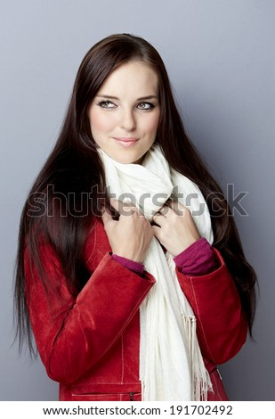 Portrait of a young smiling casual woman with long brunette hair on gray studio background, wearing red suede leather jacket and white scarf  - stock photo